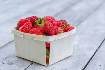 Box of freshly picked ripe red strawberries on a wooden table.