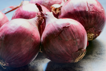 group of fresh red onions on a gray kitchen desk