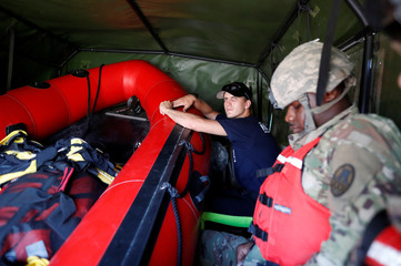 Quapaw Tribe Fire and Rescue Swift Team member Matt Walker rides in the back of a National Guard transport vehicle to help victims of flood waters in the aftermath of Hurricane Florence in Whiteville, North Carolina