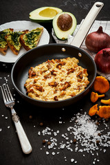 delicious scrambled eggs with chanterelles straight from the forest in a pan and bread with avocado on a wooden kitchen table