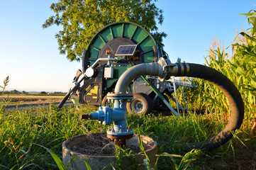 An ecological agricultural irrigation system with a big hose reel and photovoltaic solar panel at dawn