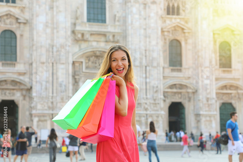 4de14f4152f7f Shopping woman excited happy in front of Milan Cathedral, Italy. Shopper  girl holding shopping