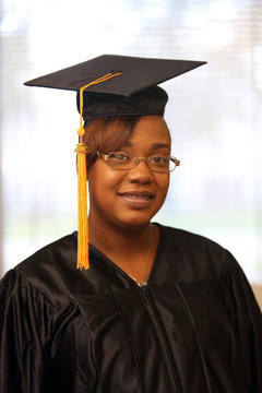 Attractive African American college graduate in cap and gown, law school graduate, law degree