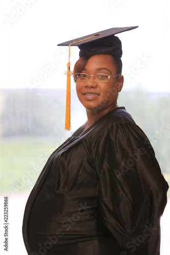 cd3937d1908 Attractive pregnant African American college graduate in cap and gown