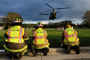 Local fire department personnel brace themselves from the backwash of a U.S. Army CH-47 Chinook helicopter as it takes off after delivering food and water to a community isolated by the effects of Hurricane Florence, now downgraded to a tropical depression