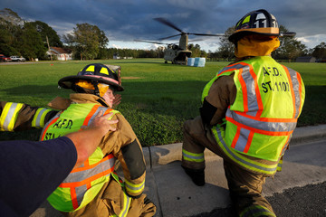 Local fire department personnel brace themselves from the backwash of a U.S. Army CH-47 Chinook helicopter as food and water is delivered to a community isolated by the effects of Hurricane Florence, now downgraded to a tropical depression, in Atkinson, No