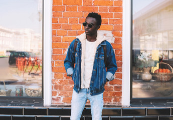 Wall Mural - Fashion african man wearing jeans jacket, backpack poses on city street, brick wall background