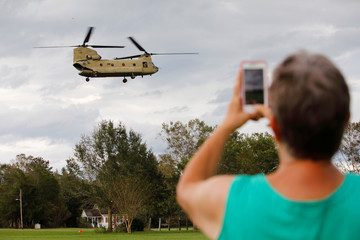 A local resident films a U.S. Army CH-47 Chinook helicopter arriving to deliver food and water to a community isolated by the effects of Hurricane Florence, now downgraded to a tropical depression, in Atkinson, North Carolina