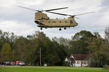 Debris rises from the backwash of U.S. Army CH-47 Chinook helicopter arriving to deliver food and water to a community isolated by the effects of Hurricane Florence, now downgraded to a tropical depression, in Atkinson, North Carolina