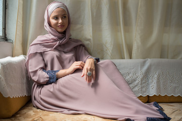 Young woman in hijab sitting on couch