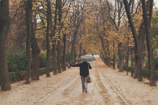 Man walking through the park in the rain, Madrid, Spain