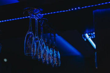 Low angle view of champagne glasses hanging on a glass hanger in a bar
