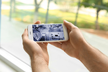 Man holding mobile phone with blank screen on blurred background, closeup. Mockup for design