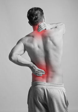 Young man suffering from neck pain on light background