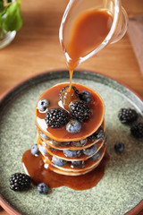 Pouring syrup onto tasty pancakes with berries on plate