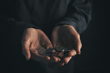 Poor woman holding coins on dark background, closeup