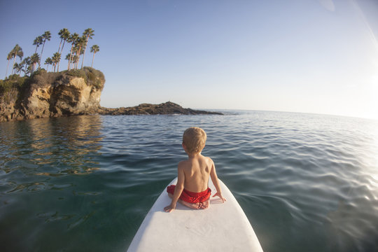 Boy sitting on a paddleboard, Orange County, California, United States