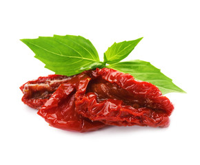 Tasty sun dried tomatoes with green leaves on white background