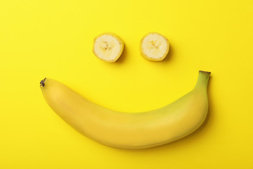 Funny flat lay composition with bananas on color background