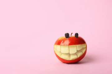 Funny smiling apple on color background. Space for text
