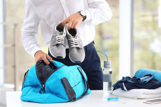 Young businessman packing sports stuff for training into bag in office