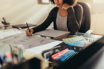 Female architect working new designs at her work desk Wall mural