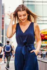 Young Eastern European Woman with long brawn hair traveling in New York City, wearing blue sleeveless, v neck, jumpsuit, walking on street in middletown of Manhattan, looking down, thinking, smiling..