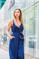 Young Eastern European Woman with long brown hair traveling in New York, wearing blue sleeveless jumpsuit, hands in pockets, walking on street by glass wall with reflections in Manhattan, New York..