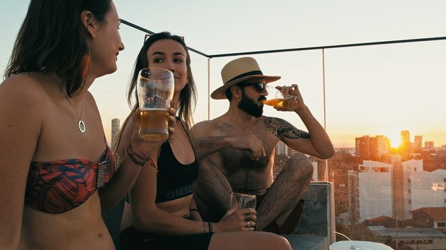young woman and man people enjoying a beer and the company at a rooftop bar above the city with beautiful view with a cute pet dog