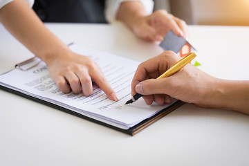 Estate agent pointing finger on document showing where to sign. Signing a paper document for buying house.Real estate, home loan and insurance concept