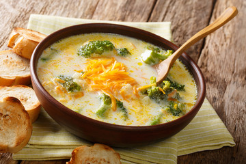 Delicious cheesy broccoli soup with vegetables in a bowl with toast close-up. horizontal