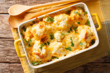Delicious baked fresh cauliflower with cheese sauce close-up in a baking dish. horizontal top view