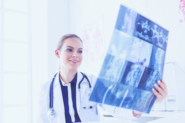 Young attractive female doctor looking at x-ray image