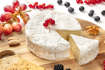 A closeup photo of Camembert cheese with fruits and nuts, shot on a white background