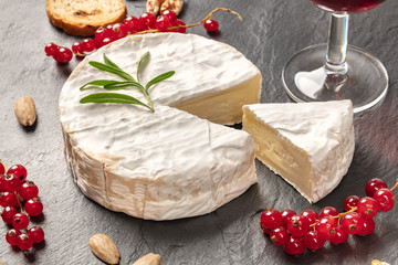 A photo of Camembert cheese with a glass of red wine, fruits and nuts, shot on a black background with copy space