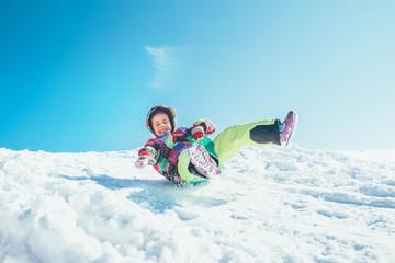 Happy little girl slides down from the snow slope. Enjoying the winter sledding time