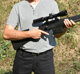 Man stands in hand with a large shotgun