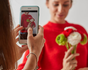 The girl takes a photo on the phone of a young pretty woman with a bouquet of fresh flowers on a gray background.