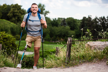 Overjoyed young man with prosthesis trying Nordic walking