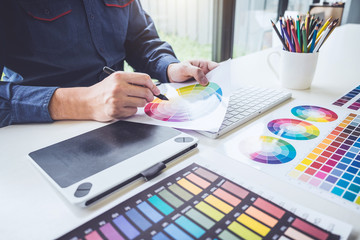 Image of male creative graphic designer working on color selection and drawing on graphics tablet at workplace with work tools and accessories