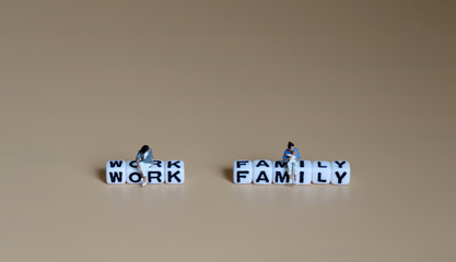 A miniature woman sitting on a cube of 'WORK' word and a miniature woman with baby sitting on a cube of 'FAMILY' word.