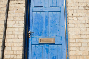 Brass door letterbox on a blue vintage front door on a  yellow brick wall