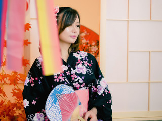 Portrait of attractive asian woman wearing traditional Japanese Kimono holding round paper fan in hand, standing in front of sliding door, waiting someone coming home, lifestyle of authentic people.