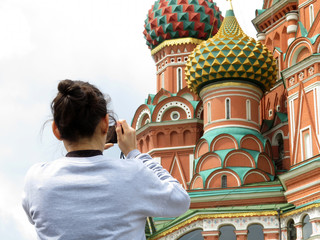 Woman tourist taking pictures with smartphone the St. Basil's cathedral on Red square in Moscow. Tourism in Russia, russian landmarks and symbols