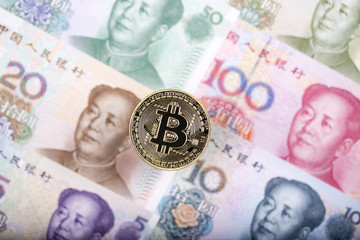 Bitcoin coin on the background of Chinese banknotes