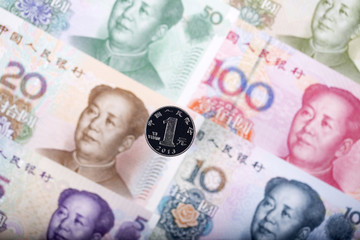 Yuan coin on the background of Chinese banknotes