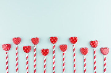 Red hearts and striped straws with copy space on trendy color mint backdrop as playful modern valentine's day background.