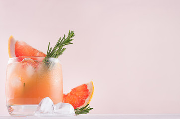 Foto op Aluminium Cocktail Cold grapefruit cocktail decorated twig rosemary and slice citrus closeup on pink background.