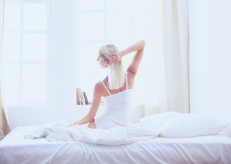 Woman stretching in bed after wake up, back view