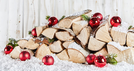 Winter stockpile of wood logs in snow at Xmas